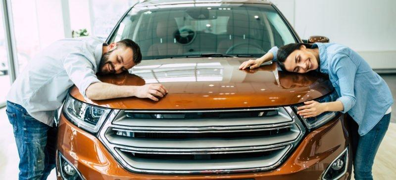Young couple buying a new car in dealership