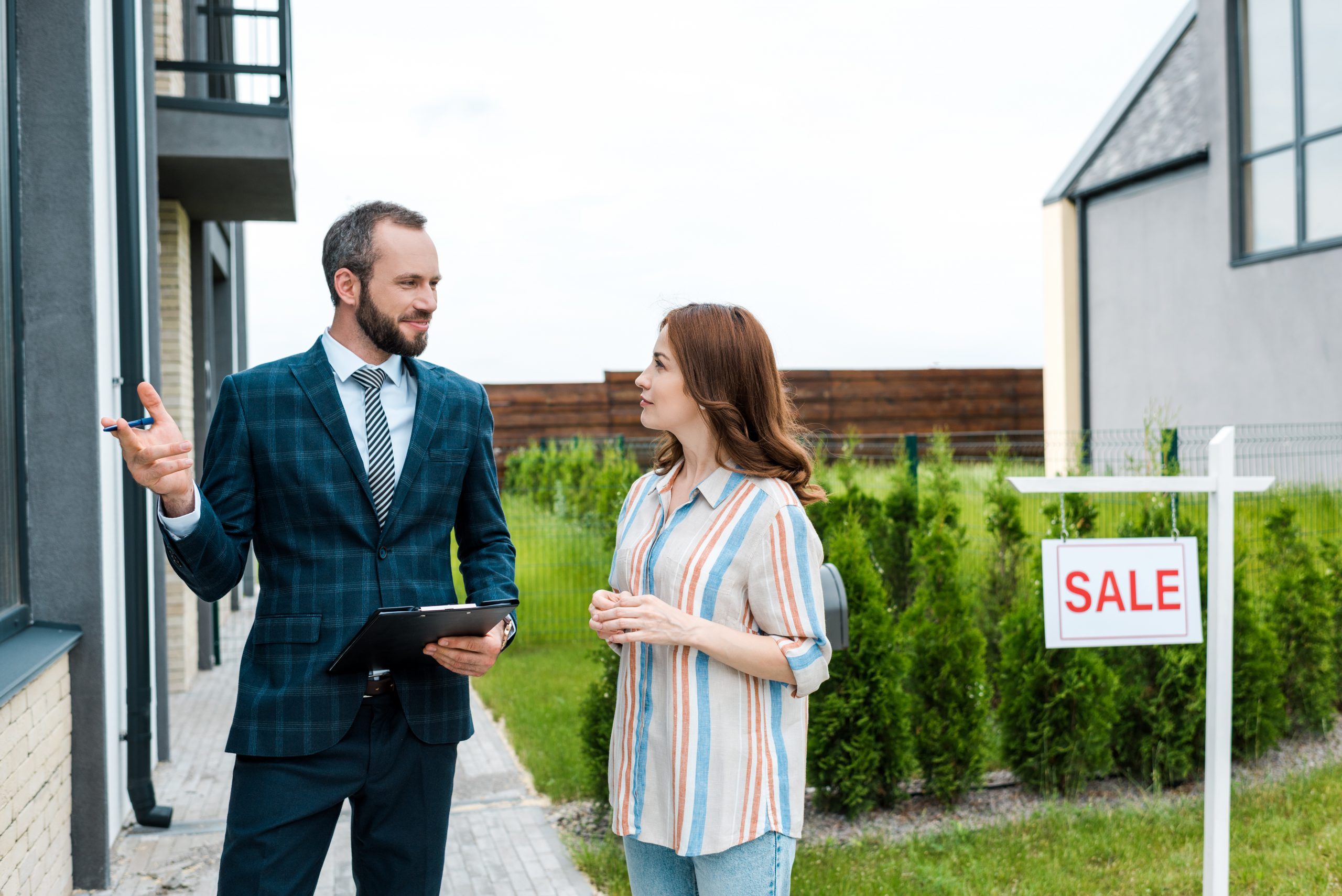 handsome bearded broker holding clipboard and gesturing near attractive woman and board with sale letters
